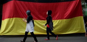 BERLIN - JULY 07: Two young Muslim women walk by a pub draped in a German flag in the Arab and Turkish-heavy neighborhood of Neukoelln during the FIFA 2010 World Cup match between Germany and Spain on July 7, 2010 in Berlin, Germany. Many immigrants in Germany identify strongly with the German national team, in part because many of the team's members have African, Arab, Turkish or East European roots. (Photo by Sean Gallup/Getty Images)
