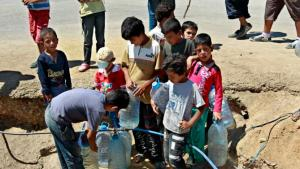 Syrian refugees boys fill up their water bottles, at a temporary refugee camp in the eastern Lebanese town of Faour near the border with Syria, Lebanon, Wednesday, Aug. 28, 2013. U.N. chemical weapons experts headed to a Damascus suburb on Wednesday for a new tour of areas struck by a purported poison gas attack, activists said, as the U.S. laid the groundwork for a possible punitive strike and the U.N. chief pleaded for more time for diplomacy. (AP Photo/Bilal Hussein)