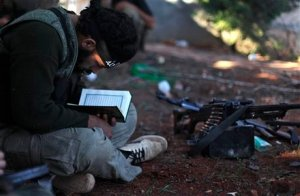 In this Thursday, Nov. 15, 2012 file photo, a Syrian rebel reads Quran during clashes with government forces in Aleppo, Syria. Through mid-2012, rebel power grew and Assad's army ramped up its response. Relentless government shelling leveled neighborhoods and killed hundreds. Regular reports emerged of mass killings by the regime or thugs loyal to it, pushing more Syrians toward armed struggle. The government, which considers the opposition terrorist gangs backed by foreign powers, denied any role, and does not respond to requests for comment on its military. The rebels, too, were accused of atrocities. (AP Photo/ Khalil Hamra, File)