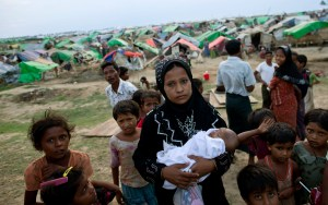 In this May 13, 2013 photo, an internally displaced Rohingya woman holds her newborn baby surrounded by children in the foreground of makeshift tents at a camp for Rohingya people in Sittwe, northwestern Rakhine State, Myanmar. Authorities in Myanmar's western Rakhine state have imposed a two-child limit for Muslim Rohingya families, a policy that does not apply to Buddhists in the area and comes amid accusations of ethnic cleansing in the aftermath of sectarian violence. (AP Photo/Gemunu Amarasinghe) ** Usable by LA and DC Only **