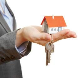 Hand einer Frau hält kleines Haus und zwei Schlüssel
